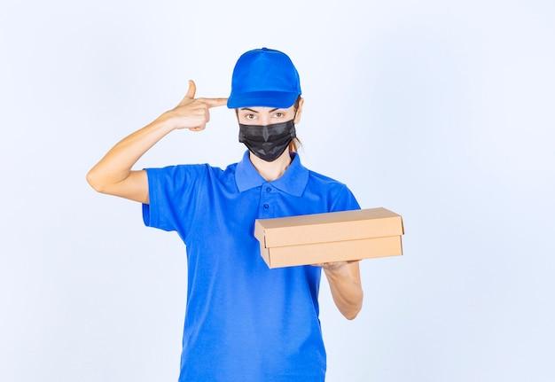 Vrouwelijke koerier in blauw uniform en gezichtsmasker met een kartonnen doos en nadenken over levering.