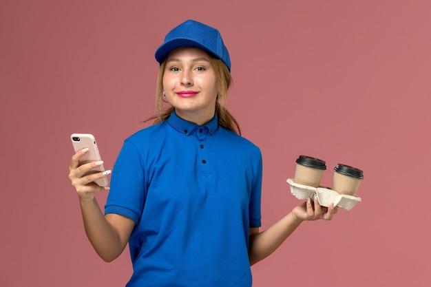 Vrouwelijke koerier in blauw uniform levering kopjes koffie te houden en met behulp van haar telefoon met glimlach op roze, uniforme levering servicemedewerker