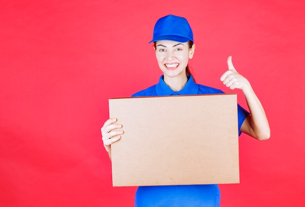 Vrouwelijke koerier in blauw uniform met een kartonnen afhaalpizzadoos en een teken van plezier