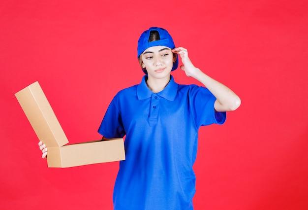 Vrouwelijke koerier in blauw uniform met een open kartonnen afhaaldoos en ziet er verward uit.