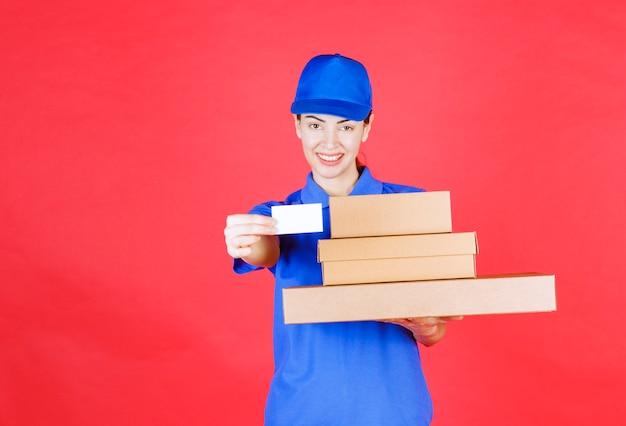 Vrouwelijke koerier in blauw uniform met een voorraad kartonnen dozen en haar visitekaartje.