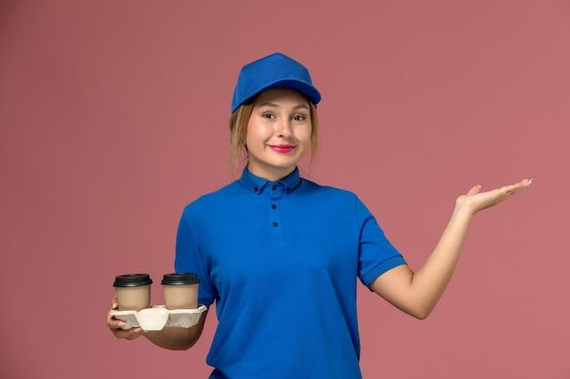 Vrouwelijke koerier in blauw uniform met kopjes koffie met een lichte glimlach op roze, service uniforme levering baan
