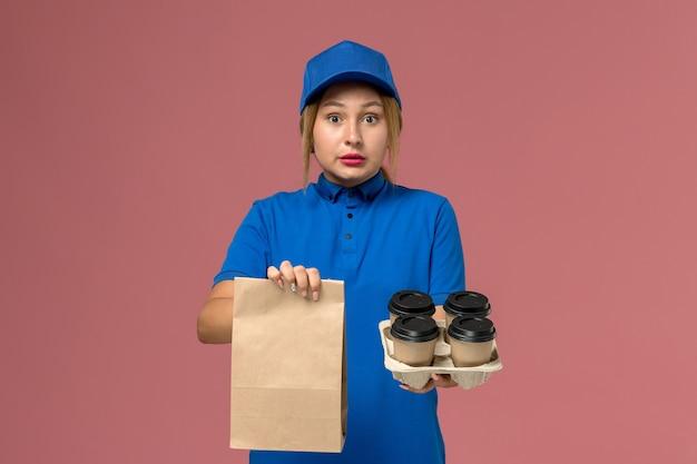 Vrouwelijke koerier in blauw uniform met voedselpakket en bruine levering kopjes koffie op roze, service uniforme bezorger