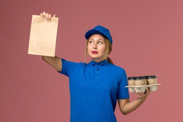 Vrouwelijke koerier in blauw uniform met voedselpakket en bruine levering kopjes koffie op roze, service uniforme levering baan