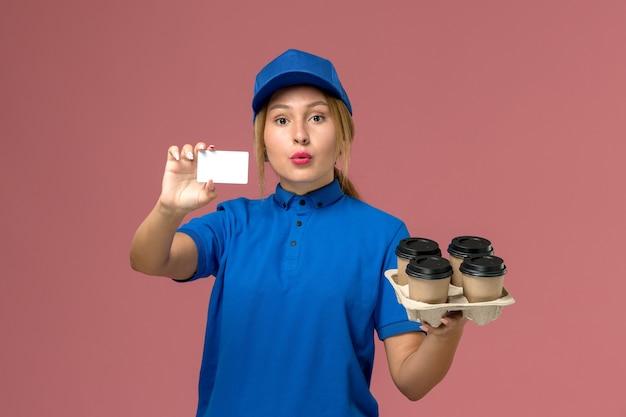 Vrouwelijke koerier in blauw uniform met witte kaart samen met bruine levering kopjes koffie op lichtroze, service baan uniforme levering