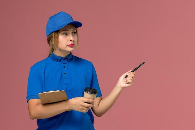 Vrouwelijke koerier in blauw uniform poseren bedrijf kopje koffie en blocnote op roze, service uniforme levering meisje werknemer