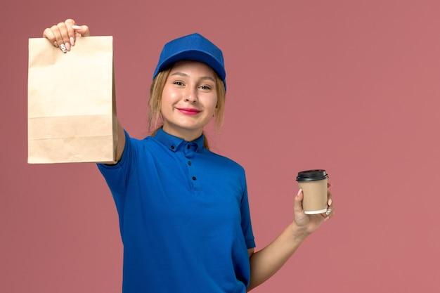 Vrouwelijke koerier in blauw uniform poseren bedrijf kopje koffie en voedselpakket met een lichte glimlach op roze, service uniforme levering baan werknemer