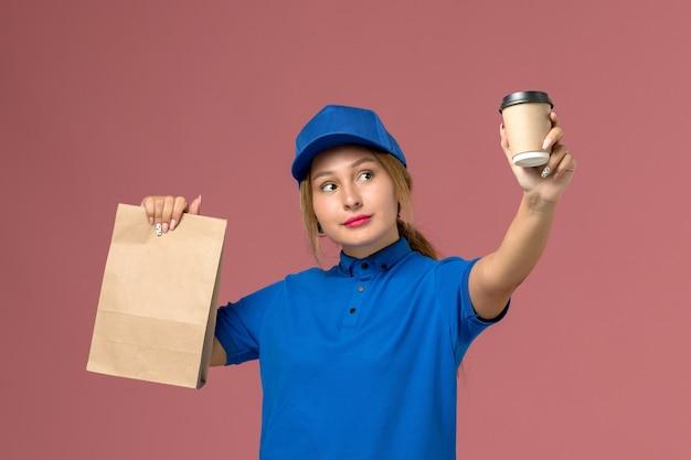 Vrouwelijke koerier in blauw uniform poseren bedrijf kopje koffie en voedselpakket op roze, service uniforme bezorger