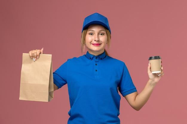 Vrouwelijke koerier in blauw uniform poseren bedrijf kopje koffie en voedselpakket op roze, service uniforme levering meisje werknemer