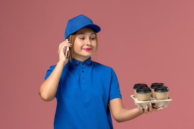 Vrouwelijke koerier in blauw uniform praten over de telefoon met bruine kopjes koffie glimlachend op lichtroze, service uniforme levering baan
