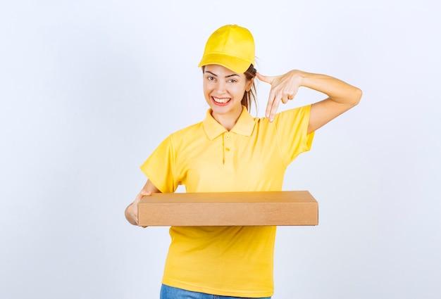 Vrouwelijke koerier in geel uniform bezorgde een kartonnen pakket op het juiste adres.