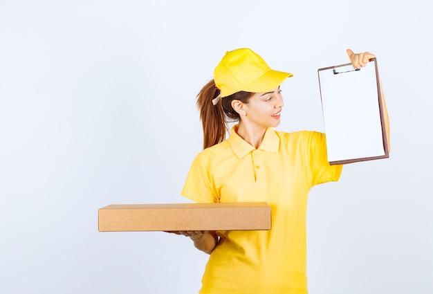 Vrouwelijke koerier in geel uniform bezorgde een pakket en vroeg de klant om te ondertekenen.