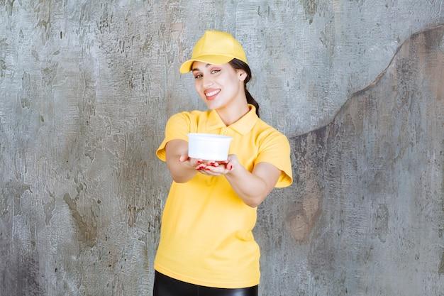 Vrouwelijke koerier in geel uniform die een afhaalbeker vasthoudt en aan de klant geeft