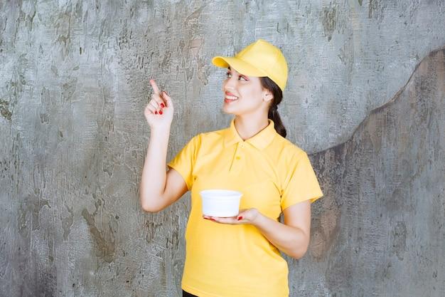 Vrouwelijke koerier in geel uniform die een afhaalbeker vasthoudt en naar iemand wijst.