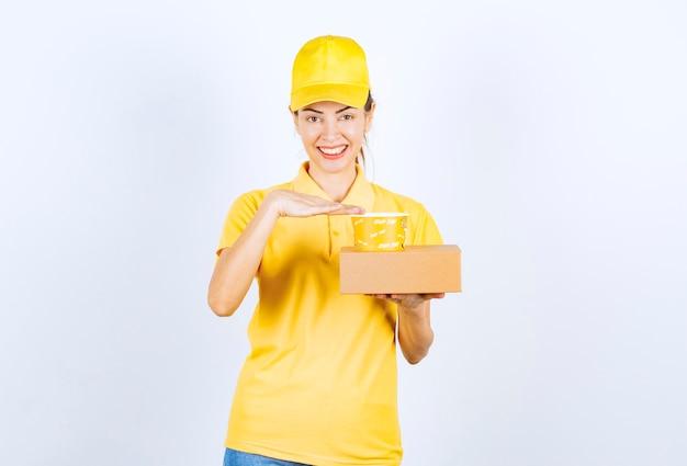 Vrouwelijke koerier in geel uniform die een afhaalbezorging doet.