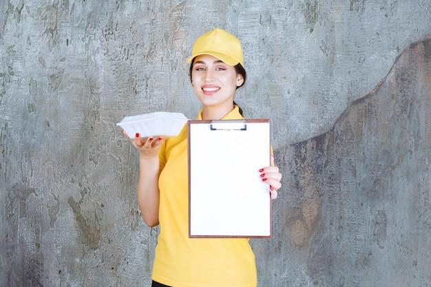 Vrouwelijke koerier in geel uniform die een afhaaldoos aflevert en om handtekening vraagt