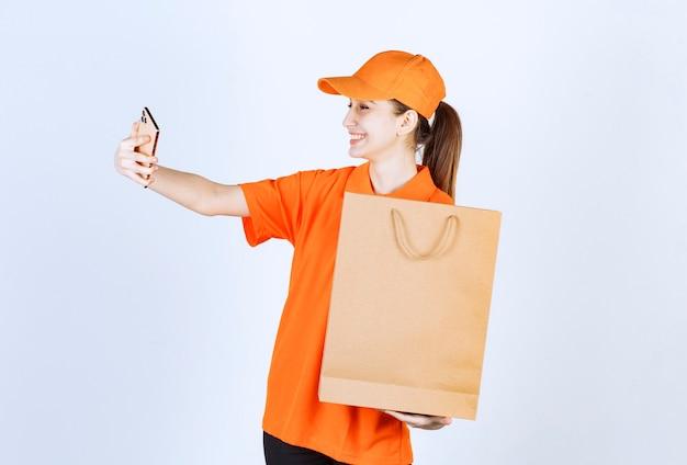 Vrouwelijke koerier in geel uniform die een boodschappentas aflevert en een videogesprek voert of haar selfie neemt.