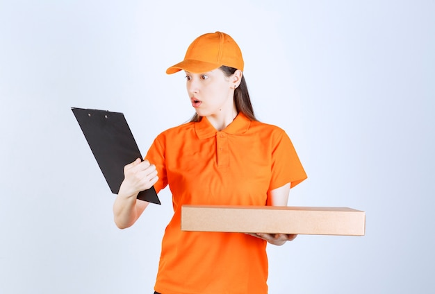 Vrouwelijke koerier in geel uniform die een kartonnen afhaaldoos vasthoudt en de adreslijst controleert en ziet er verward uit.