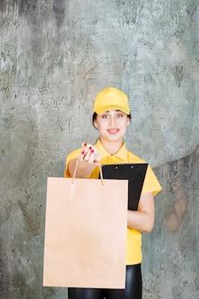 Vrouwelijke koerier in geel uniform die een kartonnen boodschappentas aflevert en een zwarte map vasthoudt.