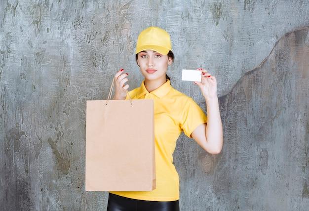 Vrouwelijke koerier in geel uniform die een kartonnen boodschappentas aflevert en haar visitekaartje presenteert