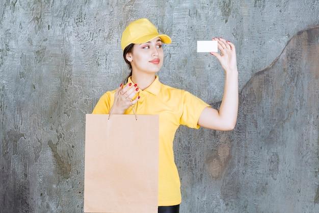Vrouwelijke koerier in geel uniform die een kartonnen boodschappentas aflevert en haar visitekaartje presenteert.