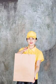 Vrouwelijke koerier in geel uniform die een kartonnen boodschappentas aflevert.