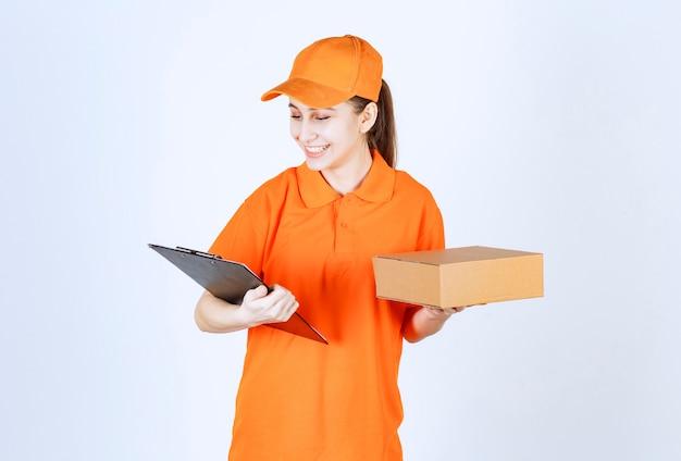 Vrouwelijke koerier in geel uniform die een kartonnen doos levert en een zwarte map vasthoudt.