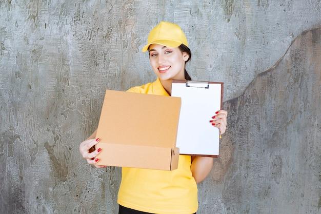 Vrouwelijke koerier in geel uniform die een kartonnen pakket aflevert en om een handtekening vraagt