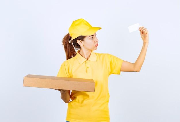 Vrouwelijke koerier in geel uniform die een kartonnen pakket vasthoudt en haar visitekaartje presenteert.
