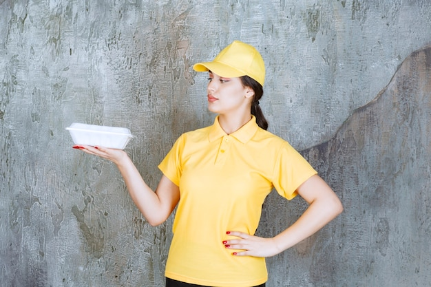 Vrouwelijke koerier in geel uniform die een witte afhaaldoos aflevert