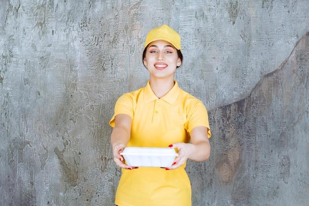 Vrouwelijke koerier in geel uniform die een witte afhaaldoos levert en aan de klant geeft