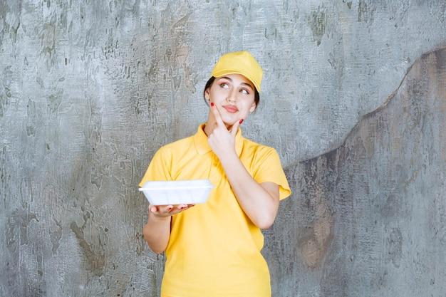 Vrouwelijke koerier in geel uniform die een witte afhaaldoos levert en er attent uitziet