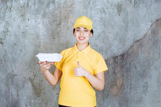 Vrouwelijke koerier in geel uniform die een witte afhaaldoos levert en geniet van het eten