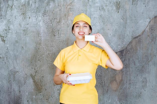 Vrouwelijke koerier in geel uniform die een witte afhaaldoos levert en haar visitekaartje presenteert