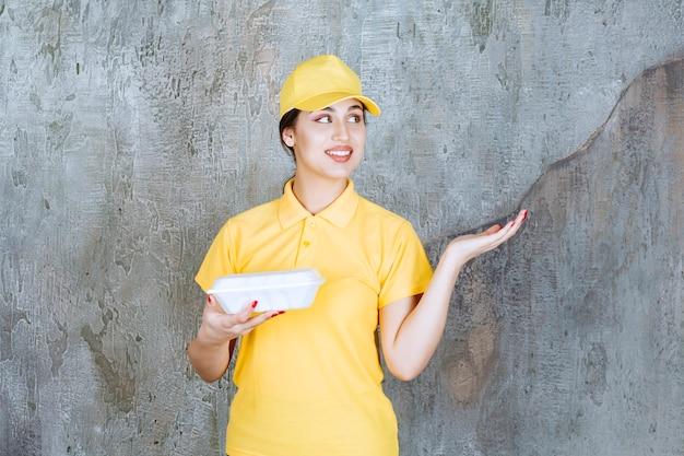Vrouwelijke koerier in geel uniform die een witte afhaaldoos levert en naar de klant wijst