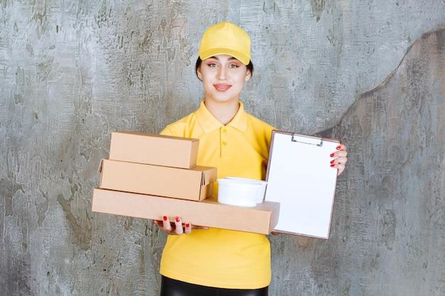 Vrouwelijke koerier in geel uniform die meerdere kartonnen dozen en afhaalbekers levert en de blanco ter ondertekening aanbiedt