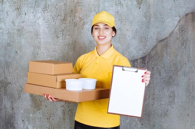 Vrouwelijke koerier in geel uniform die meerdere kartonnen dozen en afhaalbekers levert en de blanco ter ondertekening presenteert.