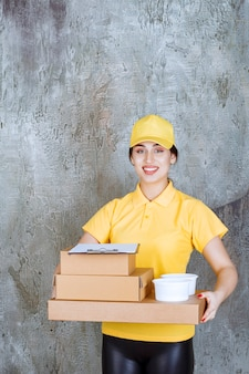 Vrouwelijke koerier in geel uniform die meerdere kartonnen dozen en afhaalbekers levert