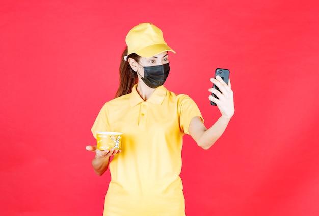 Vrouwelijke koerier in geel uniform en zwart masker bezorgt een noedelbeker en ontvangt een nieuwe bestelling op haar smartphone