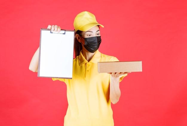 Vrouwelijke koerier in geel uniform en zwart masker die de kartonnen doos aflevert en om handtekening vraagt op de blanco