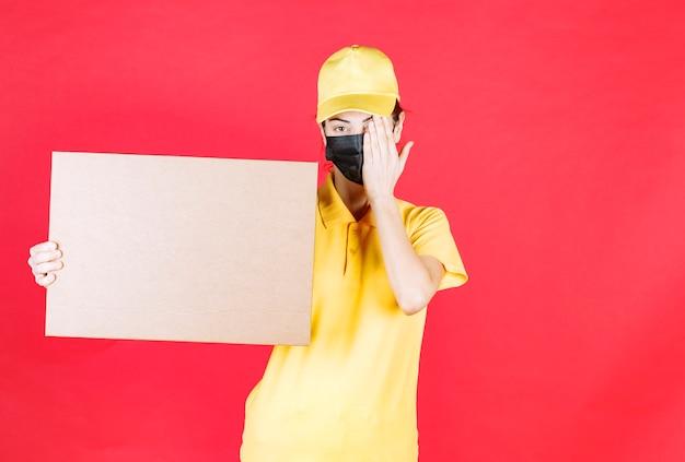 Vrouwelijke koerier in geel uniform en zwart masker die de kartonnen doos vasthoudt en één oog sluit