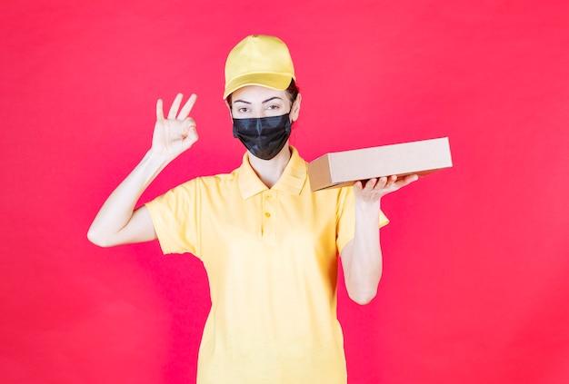 Vrouwelijke koerier in geel uniform en zwart masker die de kartonnen doos vasthoudt en een teken van plezier toont