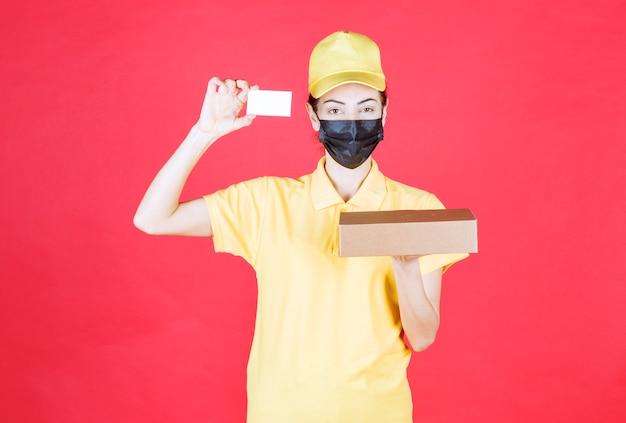 Vrouwelijke koerier in geel uniform en zwart masker die de kartonnen doos vasthoudt en haar visitekaartje presenteert