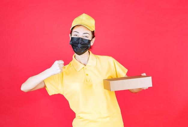 Vrouwelijke koerier in geel uniform en zwart masker die de kartonnen doos vasthoudt en haar vuist laat zien