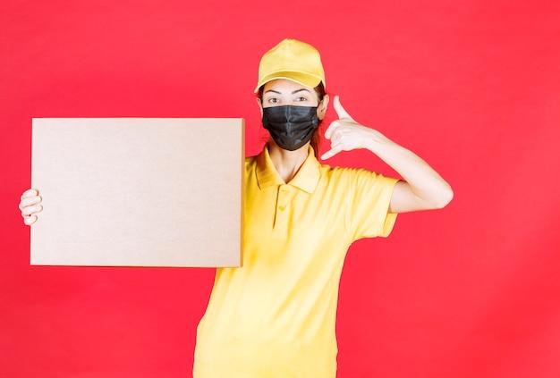 Vrouwelijke koerier in geel uniform en zwart masker die de kartonnen doos vasthoudt en om een telefoontje vraagt