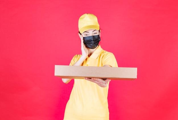 Vrouwelijke koerier in geel uniform en zwart masker die de kartonnen doos vasthoudt, ziet er verward en attent uit