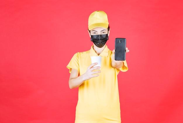 Vrouwelijke koerier in geel uniform en zwart masker die een afhaalbeker vasthoudt en met de telefoon praat of bestellingen opneemt