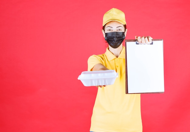 Vrouwelijke koerier in geel uniform en zwart masker die een afhaalpakket vasthoudt en de handtekeninglijst presenteert