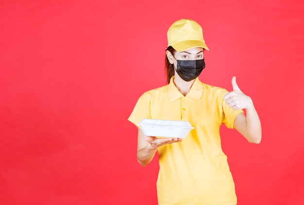 Vrouwelijke koerier in geel uniform en zwart masker die een afhaalpakket vasthoudt en een positief handteken toont