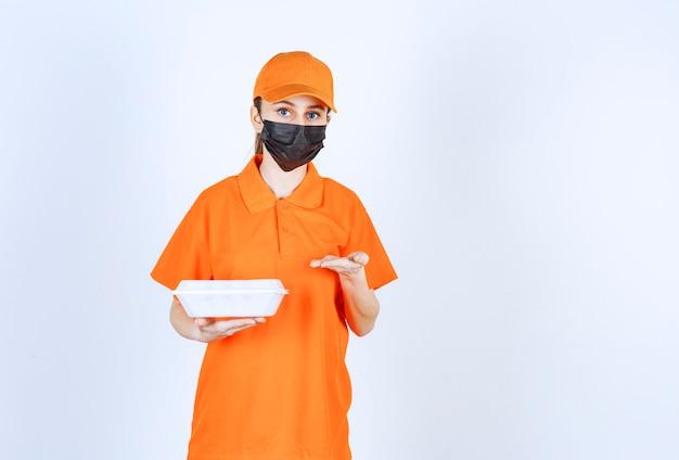 Vrouwelijke koerier in geel uniform en zwart masker die een plastic afhaalmaaltijdendoos vasthoudt en ernaar wijst.